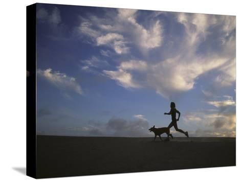 Woman and Her Dog Run Along the Beach with Beautiful Sky-Skip Brown-Stretched Canvas Print
