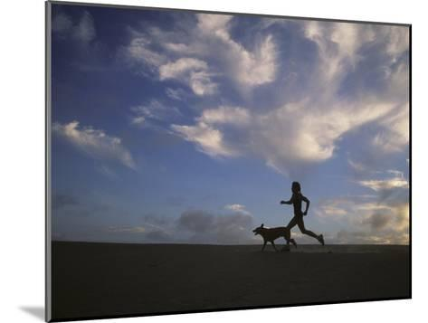Woman and Her Dog Run Along the Beach with Beautiful Sky-Skip Brown-Mounted Photographic Print