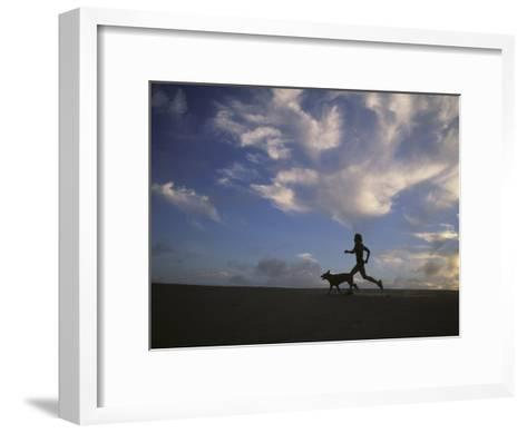 Woman and Her Dog Run Along the Beach with Beautiful Sky-Skip Brown-Framed Art Print