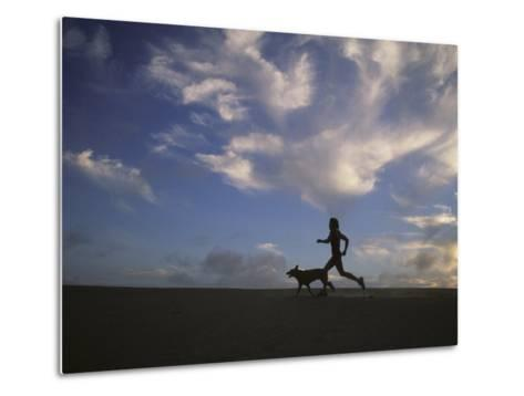 Woman and Her Dog Run Along the Beach with Beautiful Sky-Skip Brown-Metal Print