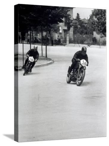 Two Motorcyclists Racing Along a Road, Otorcycles are Numbered 46 and 36-A^ Villani-Stretched Canvas Print
