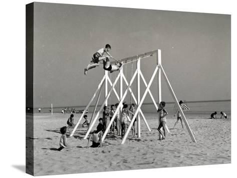 Group of Children Playing on a Swing on the Beach-A^ Villani-Stretched Canvas Print