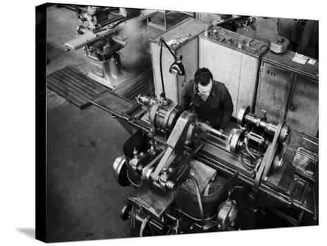 Worker Working at a Machine Inside the Innocenti Automobile Factory-A^ Villani-Stretched Canvas Print