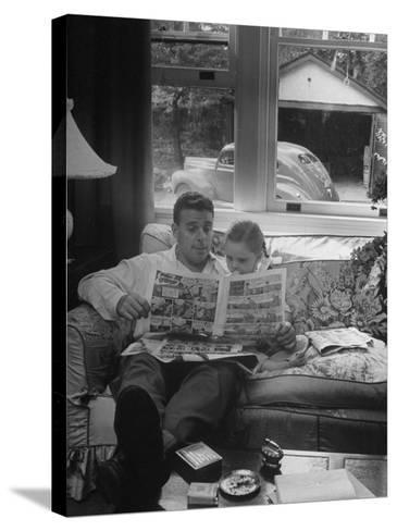 Father Sitting on Couch with Pigtailled Daughter Reading to Her the Sunday Comic Pages-Nina Leen-Stretched Canvas Print