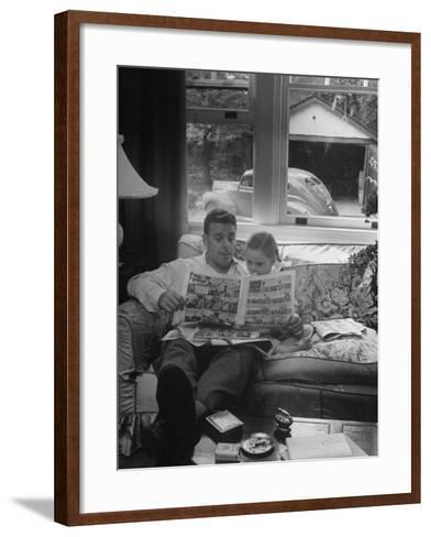 Father Sitting on Couch with Pigtailled Daughter Reading to Her the Sunday Comic Pages-Nina Leen-Framed Art Print