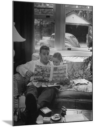 Father Sitting on Couch with Pigtailled Daughter Reading to Her the Sunday Comic Pages-Nina Leen-Mounted Photographic Print