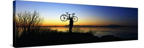 Silhouetted Cyclist Holding Bicycle over Head, River's Edge, Sunset, Alaska--Stretched Canvas Print
