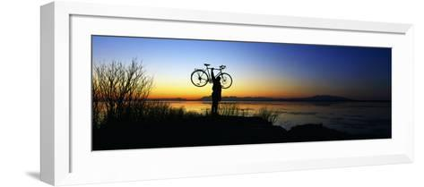 Silhouetted Cyclist Holding Bicycle over Head, River's Edge, Sunset, Alaska--Framed Art Print