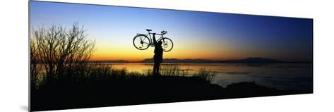Silhouetted Cyclist Holding Bicycle over Head, River's Edge, Sunset, Alaska--Mounted Photographic Print