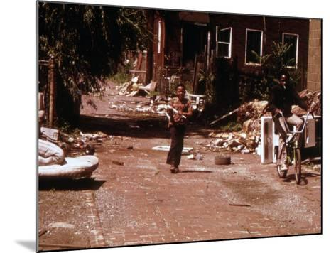 1970s America, Two Young Boys Pass Through a Trash-Strewn Alley of Chicago, Early 1973S--Mounted Photo