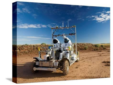 Astronauts test a surface transport vehicle in the Arizona desert--Stretched Canvas Print