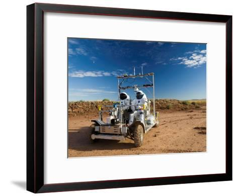 Astronauts test a surface transport vehicle in the Arizona desert--Framed Art Print
