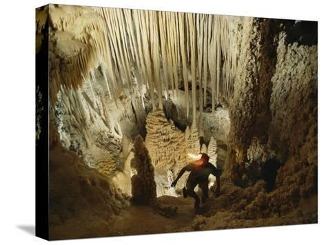 A spelunker explores a cave wearing a lanterned helmet-Michael Nichols-Stretched Canvas Print