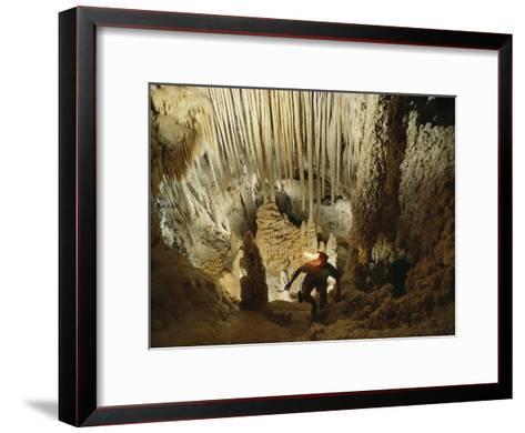 A spelunker explores a cave wearing a lanterned helmet-Michael Nichols-Framed Art Print