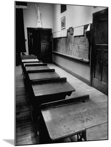 Looking Down Row of Empty Scarred Old Fashioned Desks in Schoolroom-Walter Sanders-Mounted Photographic Print