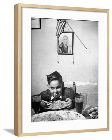 Boy Eating Spaghetti under Picture of His Brother Who Died During Invasion of Sicily--Framed Art Print