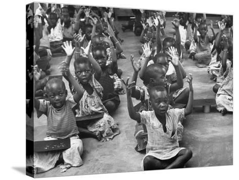 Children Raising their Hands in the Air During Kipuchi Kindergarten Classes-Dmitri Kessel-Stretched Canvas Print