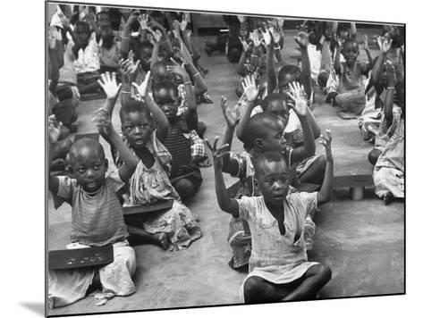 Children Raising their Hands in the Air During Kipuchi Kindergarten Classes-Dmitri Kessel-Mounted Photographic Print