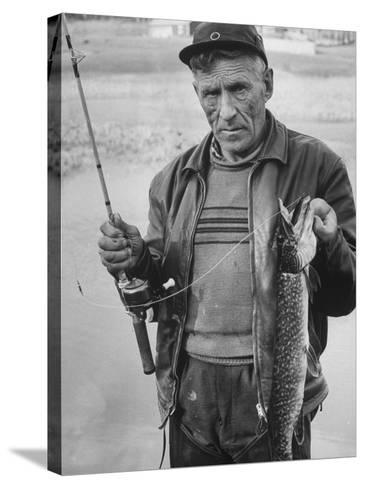 Fisherman Lauri Rapala, Who Handmakes Fishing Lures, with a Fish He Caught--Stretched Canvas Print
