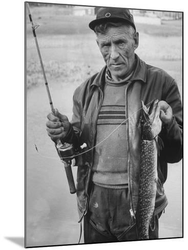 Fisherman Lauri Rapala, Who Handmakes Fishing Lures, with a Fish He Caught--Mounted Photographic Print