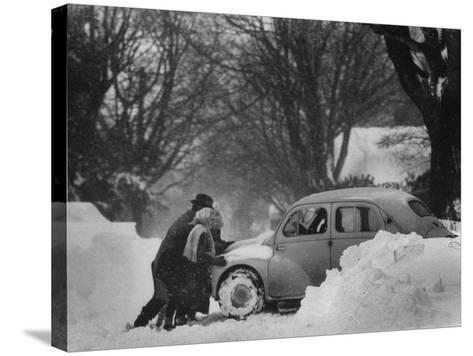 People Trying to Push a Snowbound Car--Stretched Canvas Print