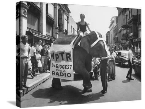 Girl Riding Elephant as a Publicity Stunt for a Radio Station-Peter Stackpole-Stretched Canvas Print