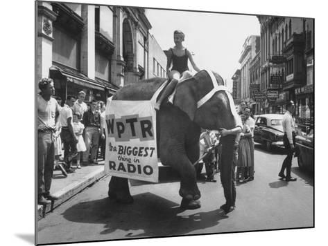 Girl Riding Elephant as a Publicity Stunt for a Radio Station-Peter Stackpole-Mounted Photographic Print