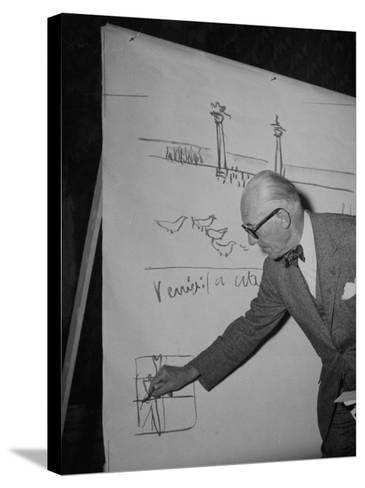 Swiss Architect Le Corbusier Standing on Stage with Notes in His Hand and Drawing on Sketch Pad--Stretched Canvas Print
