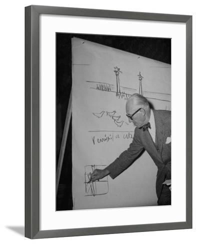 Swiss Architect Le Corbusier Standing on Stage with Notes in His Hand and Drawing on Sketch Pad--Framed Art Print