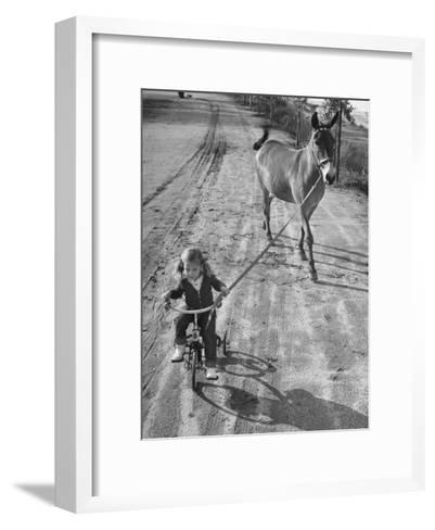Little Girl Riding Her Tricycle, Leading Francis the Mule-Allan Grant-Framed Art Print