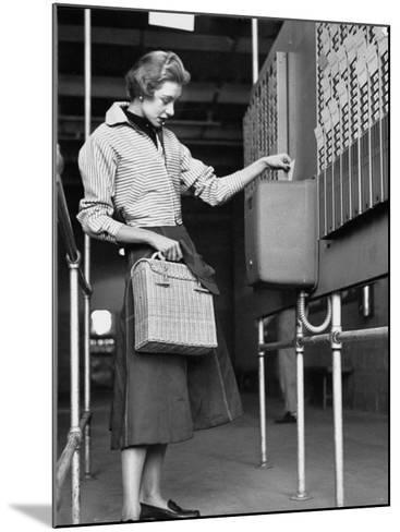 Young Lady Modeling New Line of Clothing While Getting Her Time Card Punched-Yale Joel-Mounted Photographic Print