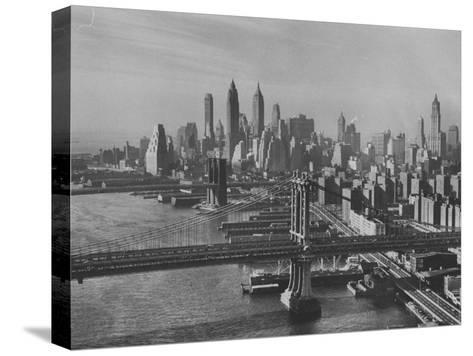 New York City Behind the Brooklyn and Manhattan Bridges That are Hovering over the East River-Dmitri Kessel-Stretched Canvas Print