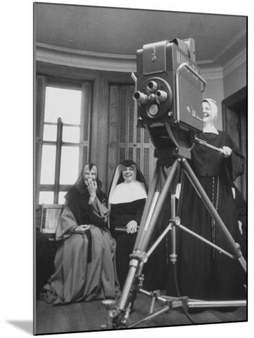 Two Nuns Smiling from the Wings While the Third Is Operating the Large TV Camera--Mounted Photographic Print