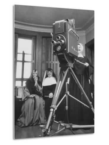 Two Nuns Smiling from the Wings While the Third Is Operating the Large TV Camera--Metal Print