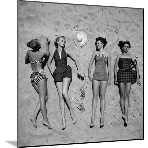 Four Models Showing Off the Latest Bathing Suit Fashions While Lying on a Sandy Florida Beach-Nina Leen-Mounted Photographic Print