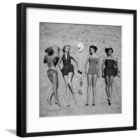 Four Models Showing Off the Latest Bathing Suit Fashions While Lying on a Sandy Florida Beach-Nina Leen-Framed Art Print
