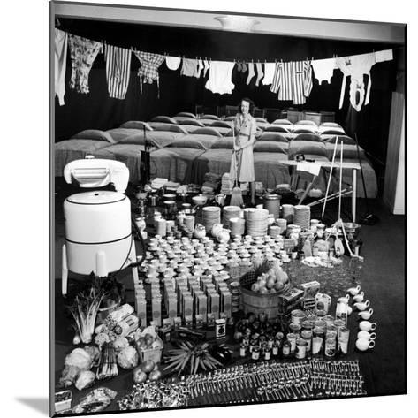 Housewife Marjorie McWeeney with Broom Amidst Display of Her Week's Housework, Bloomingdale's Store-Nina Leen-Mounted Photographic Print