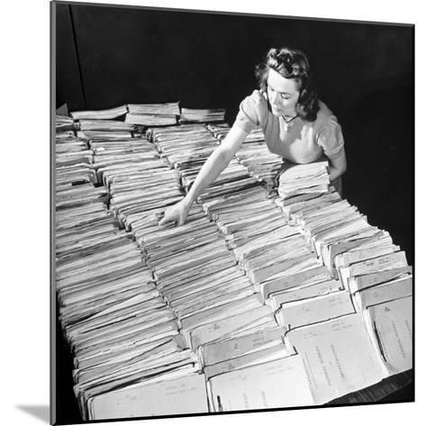 File Clerk at the Fbi Working with a Table Covered with Files--Mounted Photographic Print