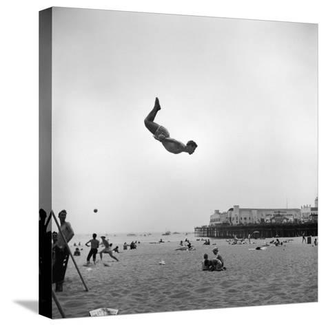 Man Flying Off a Trampoline at Santa Monica Beach-Loomis Dean-Stretched Canvas Print