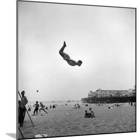 Man Flying Off a Trampoline at Santa Monica Beach-Loomis Dean-Mounted Photographic Print