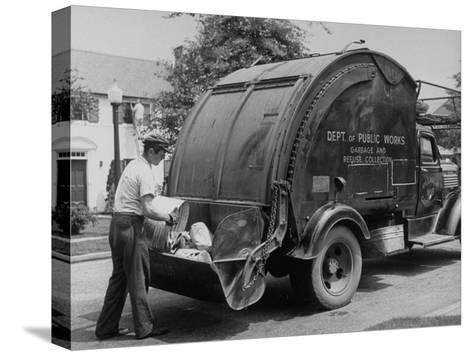 Garbage Man Emptying Trash into Back of Garbage Truck-Alfred Eisenstaedt-Stretched Canvas Print