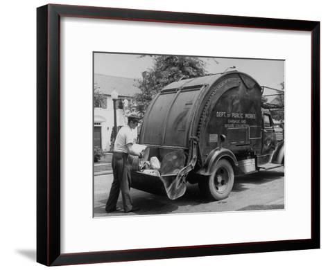 Garbage Man Emptying Trash into Back of Garbage Truck-Alfred Eisenstaedt-Framed Art Print