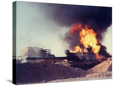 Iraqi Tank Burning While US Army Convoy Drives Past into Iraq During Gulf War-Ken Jarecke-Stretched Canvas Print