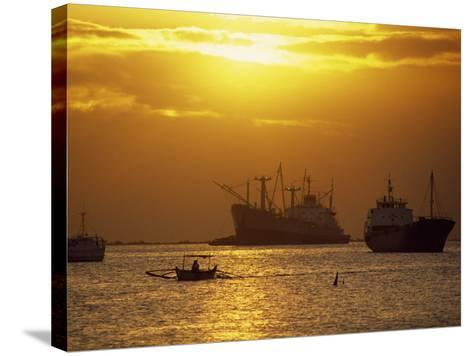 Cargo Ships and Outrigger Canoe in Manila Bay at Sunset, in the Philippines, Southeast Asia-Robert Francis-Stretched Canvas Print