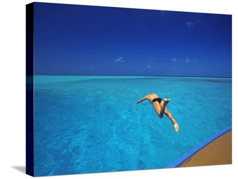 Man Jumping into Tropical Sea from Deck, Maldives, Indian Ocean-Papadopoulos Sakis-Stretched Canvas Print
