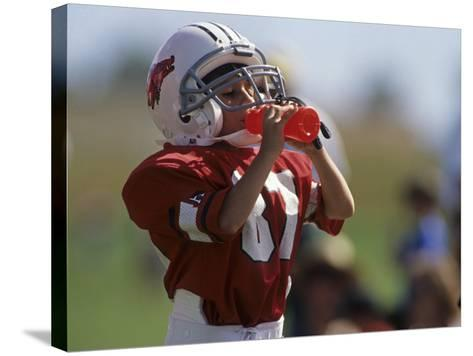 8 Year Old Boy Taking a Drink During a Football Game--Stretched Canvas Print