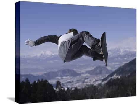 Male Snowboarder Flying over the Vert--Stretched Canvas Print