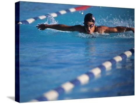 Female Swimmer Competing in a Butterfly Race--Stretched Canvas Print