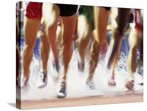 Runners Legs Splashing Through Water Jump of Track and Field Steeplechase Race, Sydney, Australia-Paul Sutton-Stretched Canvas Print