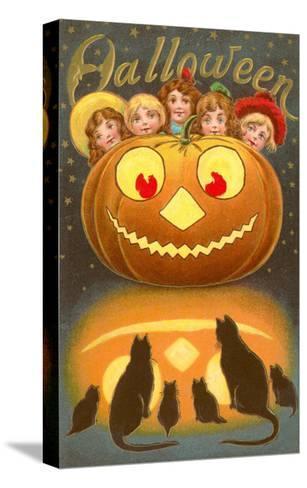 Halloween, Children behind Jack O'Lantern--Stretched Canvas Print